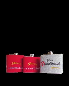 Drei Edelstahl-Flachmänner (150 ml) mit Prinz-Lebenselixier-, Prinz-Herzlwärmer- und Feiner-Hausschnaps-Schriftzug in roter und grauer Filzhülle.