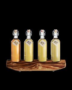 Ein rustikaler 4er-Holzständer von Prinz befüllt mit je einer 1-Liter-Flasche Alte Wald-Himbeere, Alte Marille, Alte Zwetschke und Alte Williams-Christ-Birne.