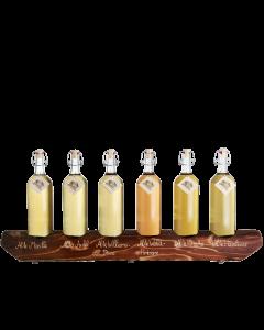 Ein rustikaler 6er-Holzständer von Prinz befüllt mit je einer 1-Liter-Flasche Alte Marille, Alter Bodensee-Apfel, Alte Williams-Christ-Birne, Alte Wald-Himbeere, Alte Kirsche und Alte Haselnuss.