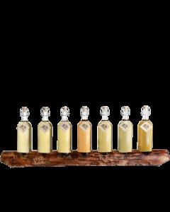 Ein rustikaler 7er-Holzständer von Prinz befüllt mit je einer 1-Liter-Flasche Alter Bodensee-Apfel, Alte Haus-Zwetschke, Alte Marille, Alte Wald-Himbeere, Alte Haselnuss, Alte Williams-Christ-Birne und Alte Kirsche.