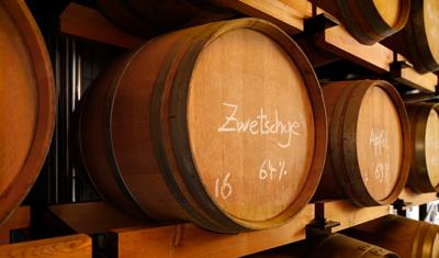 Barrique-Regal: Auf dem vordersten Prinz-Holzfass steht mit Kreide geschrieben: Zwetschge 64 %.