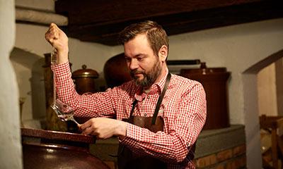 Brennmeister prüft das im Steingut gelagerte Himbeer-Destillat auf seinen Reifegrad