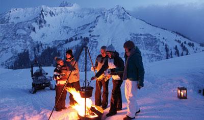 Beim Après-Ski: Junge Leute genießen vor der Skihütte Jagertee am Lagerfeuer.